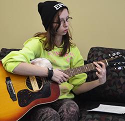 Senior Marissa Minier practices playing the guitar