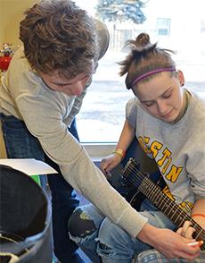 Volunteer Harrison Rice, a South Christian High School student, teaches Kelloggsville sophomore Tye Ward to play the guitar
