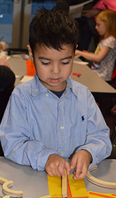 Angel Roque, 4, uses wooden shapes to make a letter