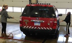 Students wash the Kentwood Fire Station's emergency vehicles