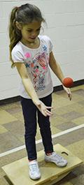 First grader Aleah Nesbitt tosses the ball
