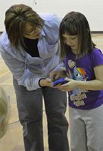 First grader Alyssa VanVolkinburg gets a little help from Brenda Munro