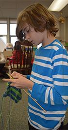 Fourth-grader Kai Manspeaker works on a scarf