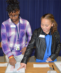 Sixth-grade bank tellers Kayla Haggerty and Regi Hovermale demonstrate how they help students open accounts