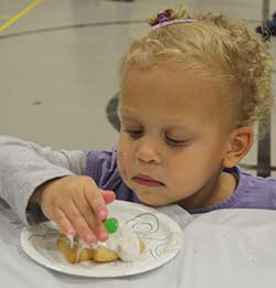 McKenna Coleman, 2, decorates a cookie at Rebel U Outreach