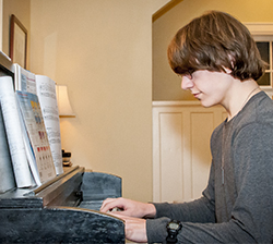 Henry Lachman uses the piano while composing