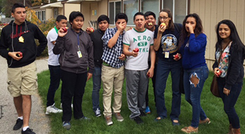 Students munch on their apples outside the greenhouse.