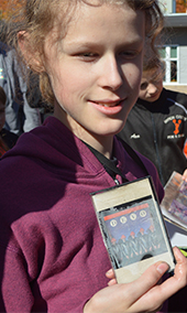 Nickels Intermediate School sixth-grader Brenna Stachnic holds a DEVO tape from the capsule