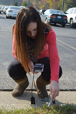 Freshman Victoria Wade tests soil temperature, data that will be merged with information from the drone