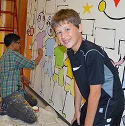 Wealthy Elementary student Oscar Osbourne poses by the mural while artist Bren Bataclan works