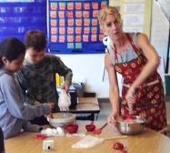 Students Miriam Vargas and Gerry Johnson mix cake with teacher Katy Andreini