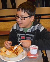 Sixth grader Dillin Le eats lunch