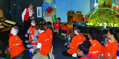 Museum docent Phyllis Vanden Berg speaks with students in Grand Rapids Public Schools' Immerse program at the Grand Rapids Public Museum's habitat exhibits. (Photo courtesy of the Grand Rapids Public Museum.)