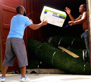 Haitian workers unload rolls of turf and diapers shipped from the United States