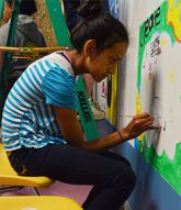 Ivory Perez works on her piece of the mural