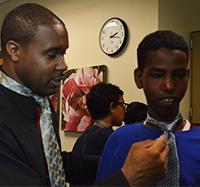 Jermale Eddie, employment and education specialist for Grand Rapids Urban League. helps Crestwood Middle School student Nur Nur tie a tie