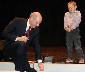 Travis VanSetters, a kindergartener at North Oakview Elementary School, gives Jamie Vollmer red tennis shoes to remind him education is all about the students