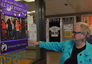 Wyoming Intermediate School social worker Christine Karas points to a poster promoting school attendance