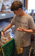 Eighth-grade student Wesley Sheller bags potatoes