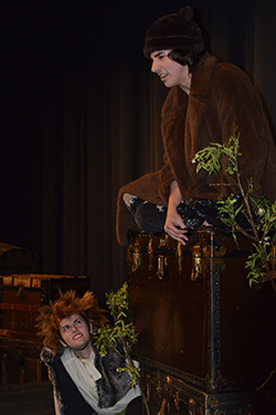 """Junior Christian Ochoa sits atop a trunk during a one-act play for """"Trunks 2"""". Junior Heidi Glynn listens to his monologue"""