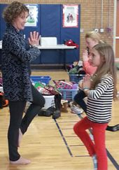 Yoga teacher Brooke Dillane stands in tree pose with fourth graders Aria Bernard and Syndey Muller