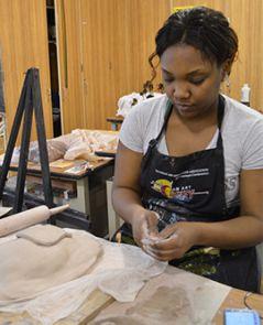 Senior Chynna Longmire works on a clay mask in art class