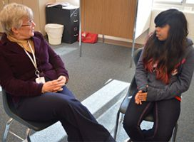 """Barb Berry chats with eighth-grade student Perla Vazquez-Juarez about her """"My Michigan Hero"""" essay."""