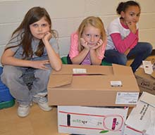 Fourth-grade students Estella Oliver, Ella Boucher and Mia Brown pretend to wait for family members after making it through the immigration processing center