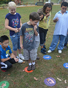 Fourth-grade student Michael Lynch tries to figure out the pattern in a game requiring students to step from circle to circle in the right order