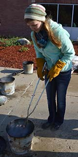 Alainie Thomas removes a raku piece from a bucket before placing it in the grass to be washed off