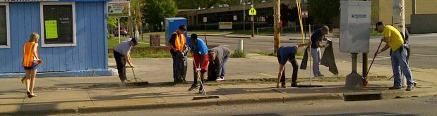 Community volunteers clean up the historic Galewood Business District, home to then Wyoming Township's first township hall, police department and library