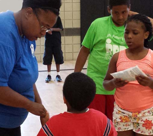 Sibley School parent Kenyana Gary helps students in an after-school program at school