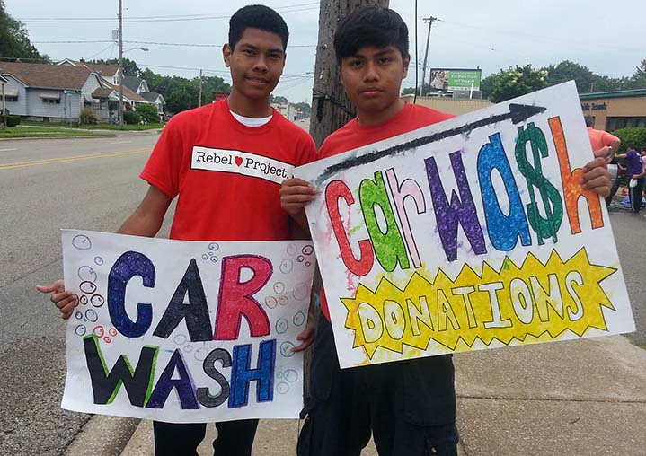Lee High School students Chance Coleman and Francisco Zainos hold up signs for their Rebel Hearts project
