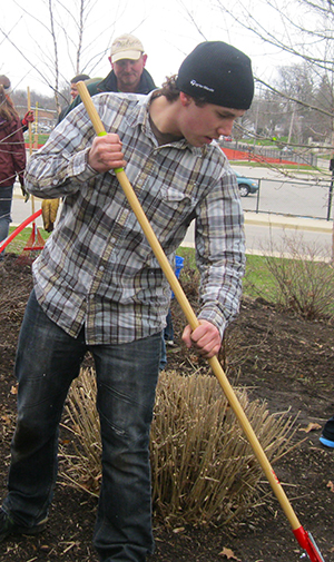 Wild and Dirty club members and volunteers clean up the East Grand Rapids High School landscape recently, prepping it for installation of native plants.