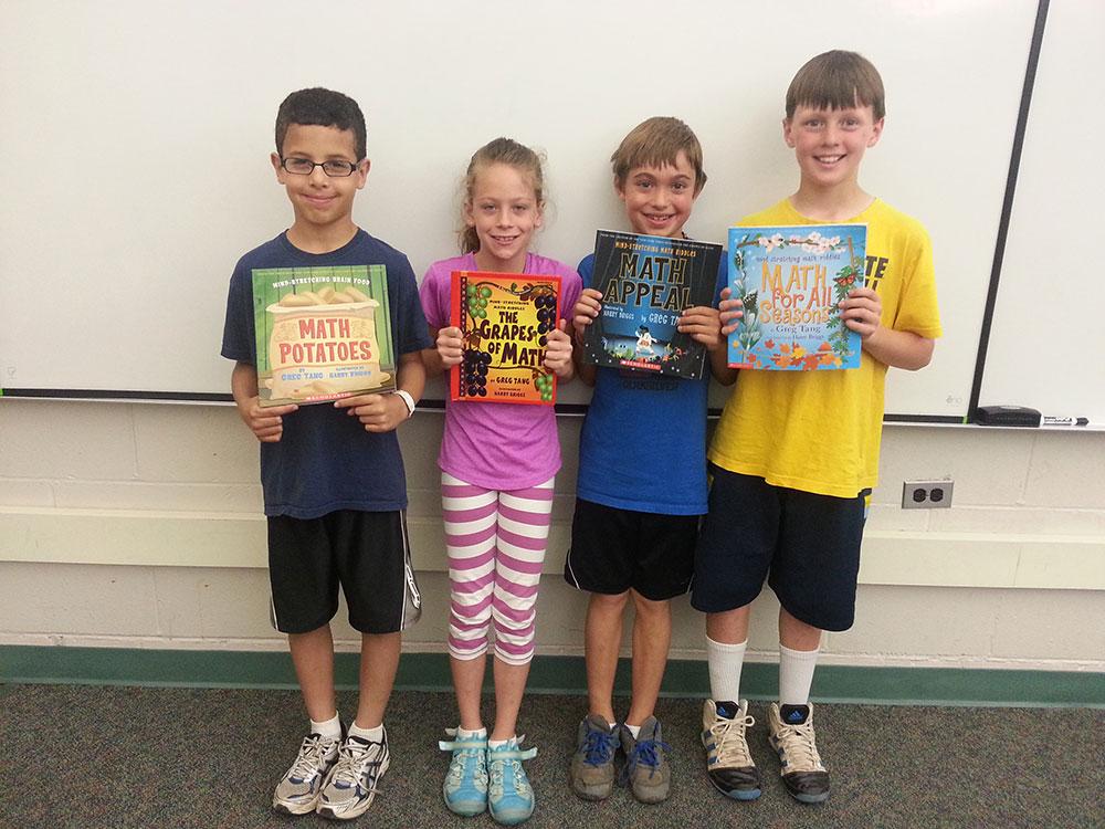 Third-graders Brendan Burns, Reece Thurston, Jack Barnes and George Samra hold up books by Greg Tang
