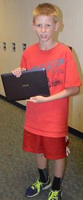 Sixth-grader Alex Rosmaria carries his device