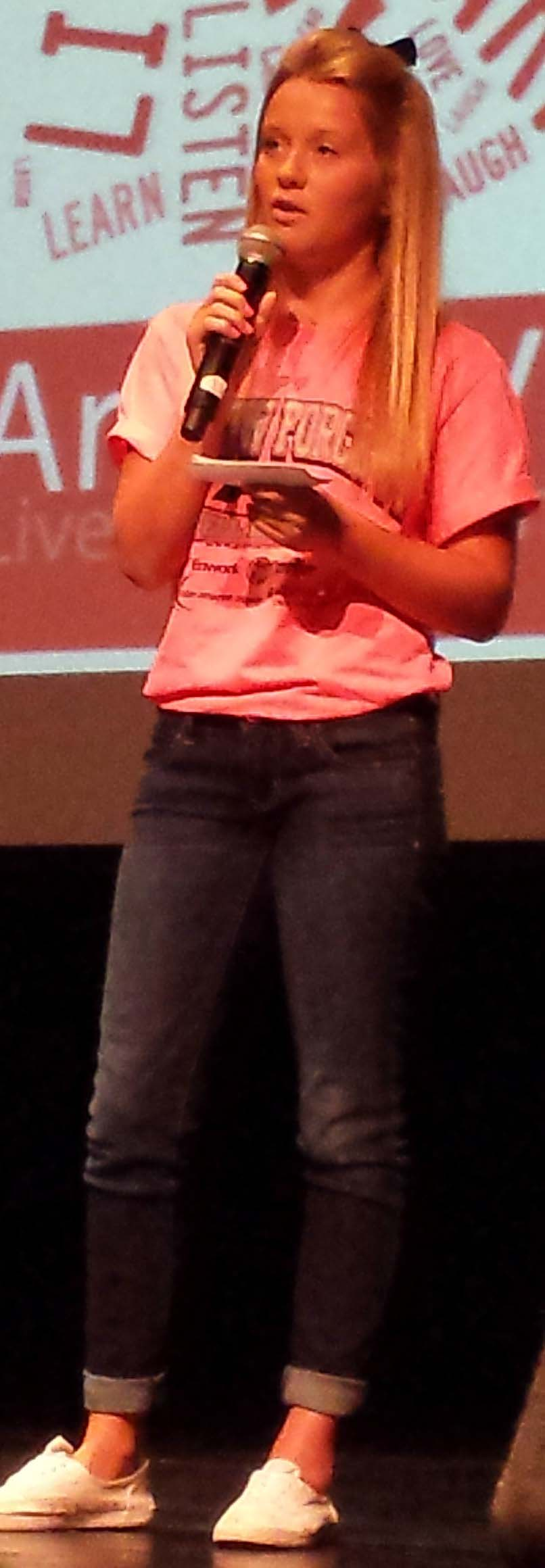 Anna Organek, a junior, addresses the assembly about her childhood experience of cancer