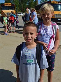 First-grader Nolan Price, front, and fifth-grader Nora Fleming, were part of the crowd of students at the bus transfer point at Kraft Meadows Elementary School. Tags are given to kindergarteners and first-graders to wear and then put on their backpacks for the rest of the year