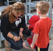 Caledonia FFA member Karah Lloyd helps pre-school students with a seed planting activity
