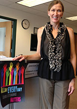 """Godfrey-Lee Psychologist Gina Kuyers stands next to posters for """"All Day Everyday,"""" a public campaign that seeks to reduce absenteeism among students in the Early Childhood Center"""