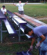 Troop members paint bleachers, part of improving the ball diamond