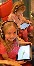 Brown Elementary kindergartner Layla Funk reads on an iPad