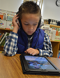 Second grader Toby Maycroft reads on an iPad