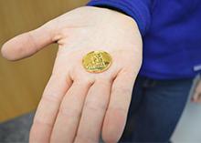 Olivia Kallil holds her golden coin