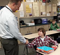 Principal Mike Ramm congratulates Devon as he takes his seat in U.S. history class