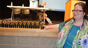 Ellen Zwarensteyn, teacher and director of debate at East Kentwood High School, arranges trophies while debaters take notes on stage