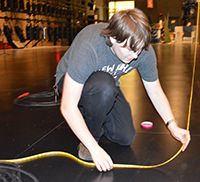 Senior Parker Brauntz takes measurements on stage