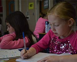 Alayna Cook, front, and Naliya Clark work on their essays