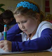Brooklyn Colclasure works on her essay in the Beach Elementary writing workshop