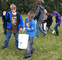 Students carry buckets in teams
